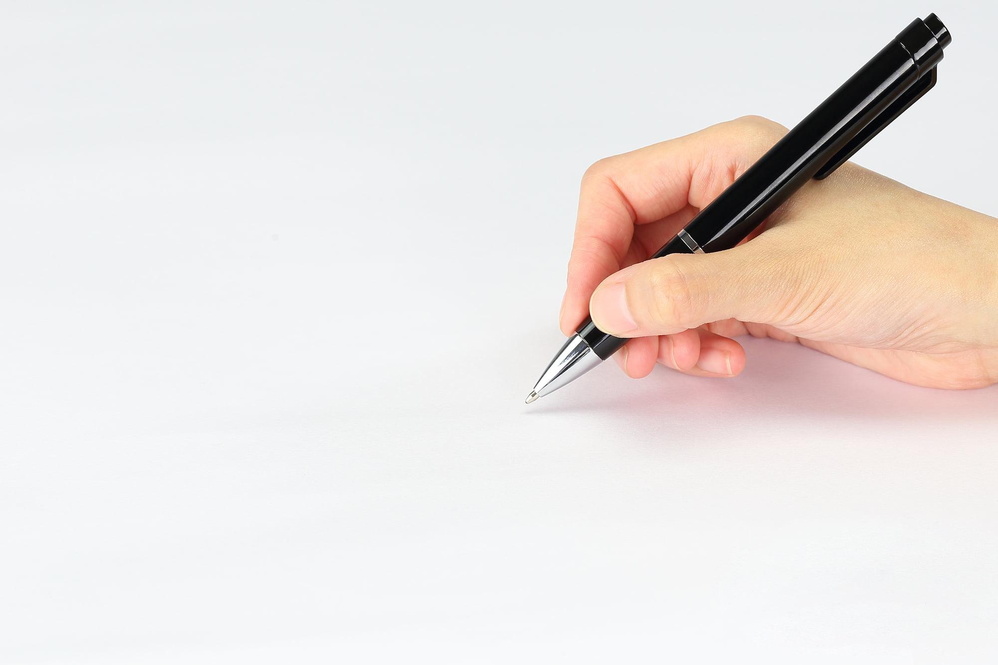 ボールペンで何かを書こうとする人の手