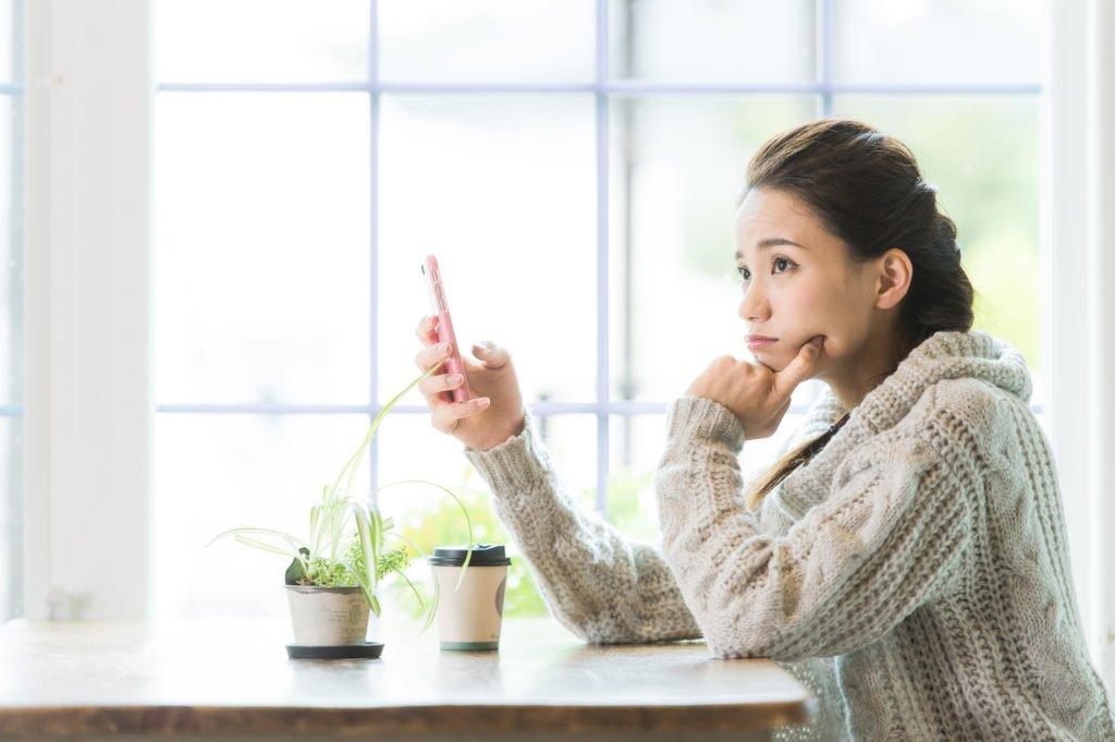 派遣-スマートフォンで派遣会社に電話をかけるか悩む女性