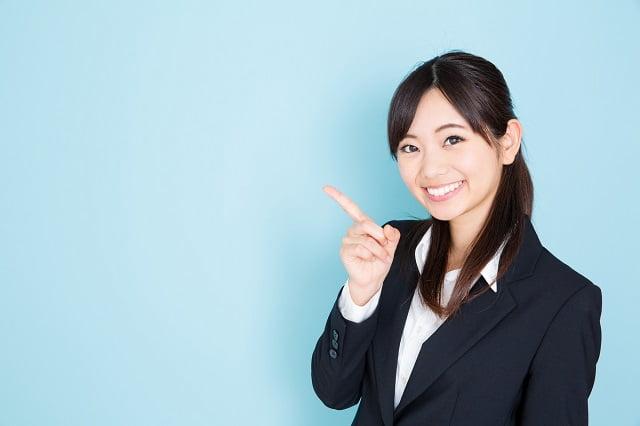 指をさす紺スーツ女性