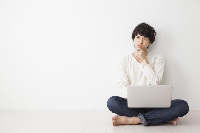 疑問に思うパソコンを持つ男性