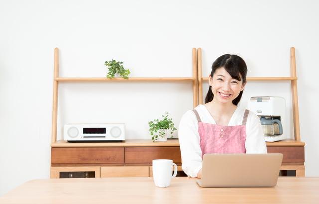 笑顔でノートパソコンを操作する主婦